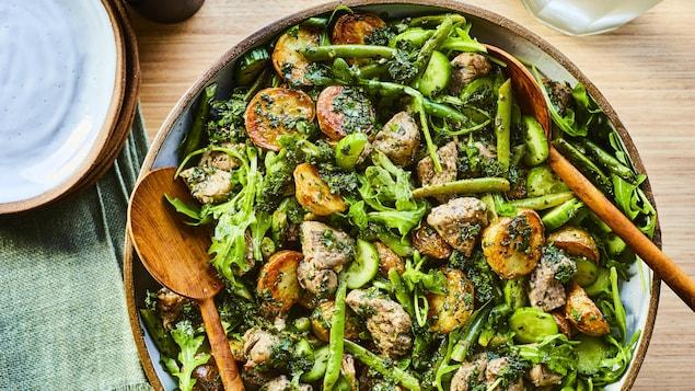 Un grand bol rempli de salade d'agneau au chimichurri avec des ustensiles de service dedans.