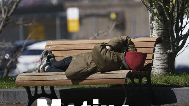 Un homme sur un banc, au soleil, avec un manteau et un capuchon.