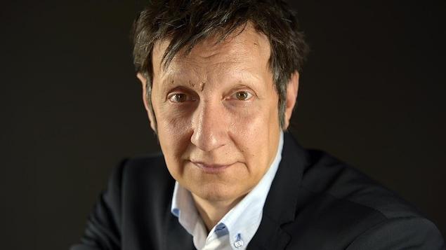 Portrait de Robert Lepage sur fond noir.