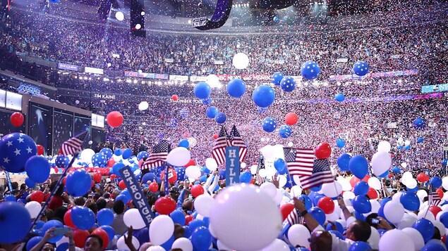 Des ballons aux couleurs du drapeau américain tombent dans un stade bondé de gens.