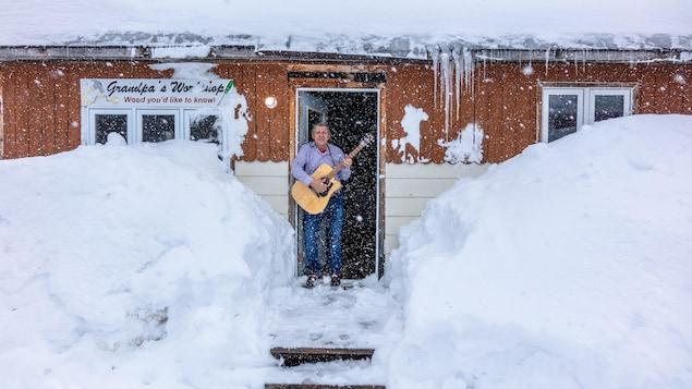 Le musicien Alister Martin tient une guitare dans sa main.