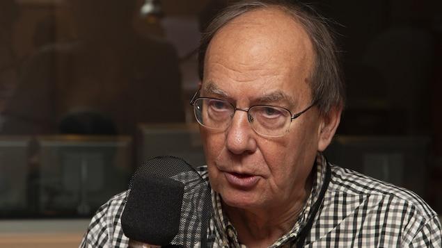Michel Fortmann devant un micro radio dans les studios de Radio-Canada.