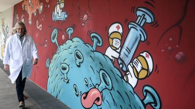 L'homme marche dehors, devant une grande murale qui illustre des employés d'hôpitaux qui tentent de vaincre un coronavirus.