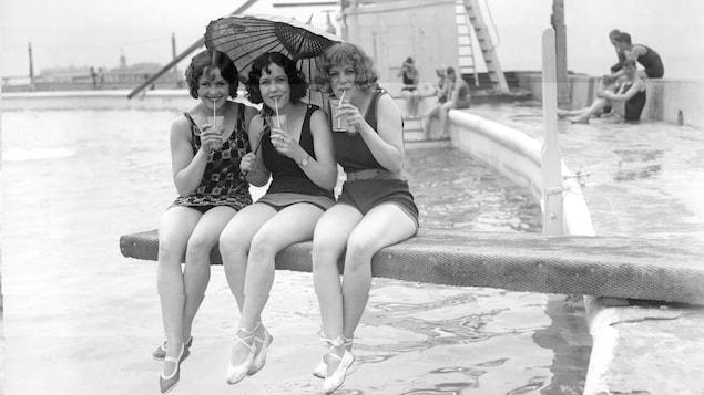 Les femmes sirotent une limonade, assises sur ce qui semblent être un tremplin. au-dessus d'un plan d'eau.