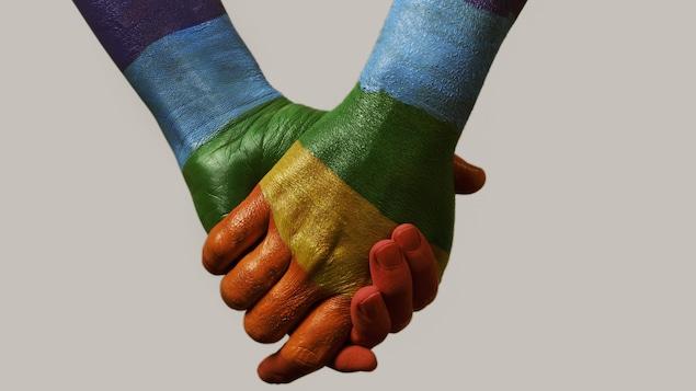 Gros plan des mains d'un couple d'homme. Elles sont aux couleurs du drapeau arc-en-ciel.