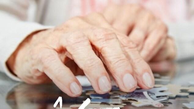 Gros plan sur les mains ridées d'une femme manipulant les pièces d'un casse-tête.