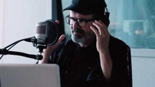 Pierre Flynn parle dans un micro dans les studios de Radio-Canada.