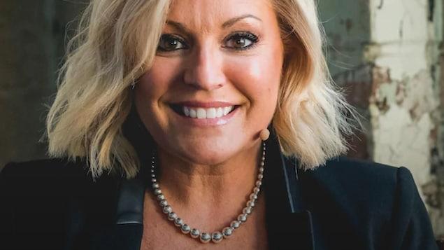 La chanteuse aux cheveux blonds pose en souriant.