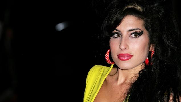 Une femme vêtue de jaune regarde vers sa gauche, sur fond noir.