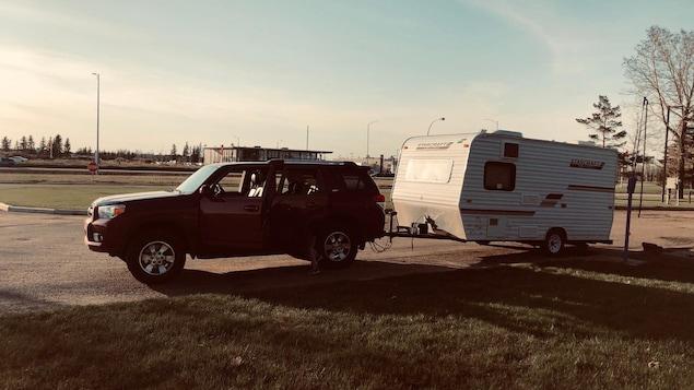 Un véhicule utilitaire sport remorquant une roulotte de camping de quelques mètres.