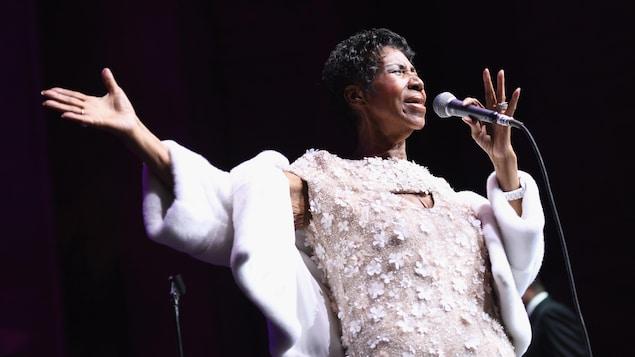 Aretha Franklin, vêtue de blanc, chante sur une scène un microphone à la main.