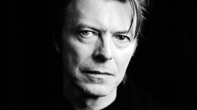 Photo en noir et blanc d'un homme d'âge mûr. Une mèche de cheveux tombe sur son front. Il a un œil de couleur pâle et un œil de couleur foncée.