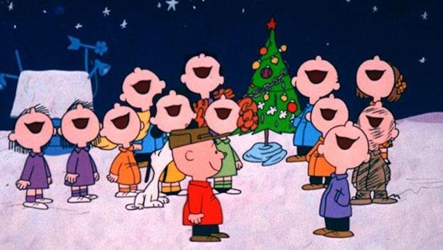 Charlie Brown sourit en regardant une chorale d'enfants chanter sous la neige.
