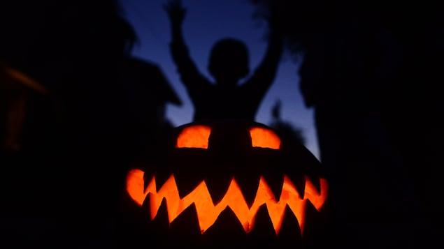 Une citrouille illuminée dans un décor sombre avec un enfant qui lève les bras en l'air.