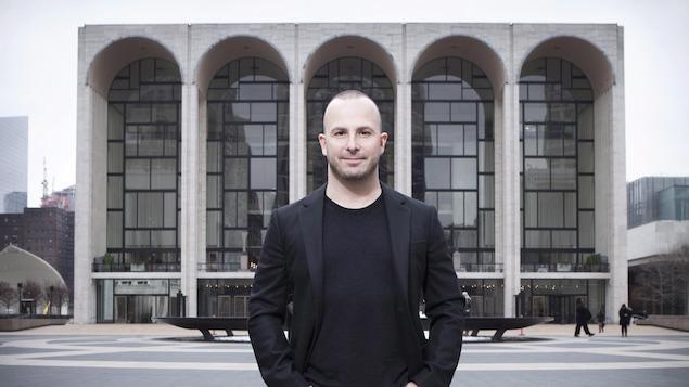 Le chef d'orchestre esquisse un sourire et pose à l'extérieur devant un grand bâtiment vitré.