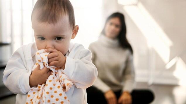 Un bébé semble sentir sa doudou pour se réconforter.