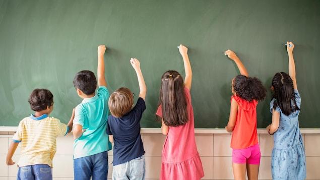 Des enfants dessinent sur un tableau avec des craies.