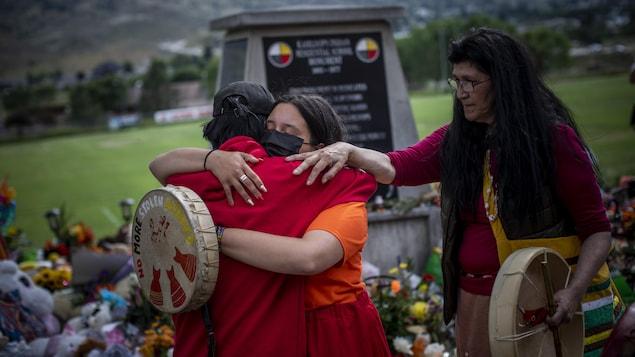 Katherine Cooper, de la Première Nation crie Mosakahiken, au Manitoba, console une amie devant un monument à la mémoire des enfants autochtones enterrés à Kamloops.