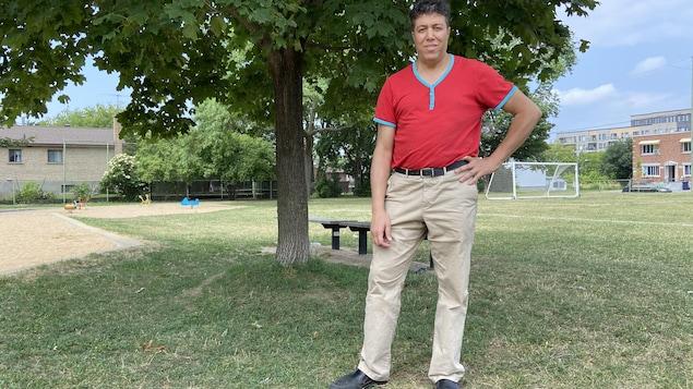 رجل يقف تحت شجرة في متنزه ويبدو في عمق الصورة مرمى كرة قدم.