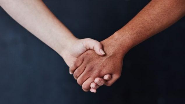 يدان بيضاء وسوداء متشابكتان.