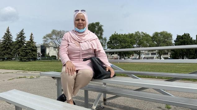 امرأة جالسة على مقعد في ملعب لكرة القدم.