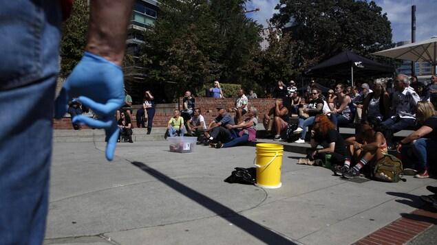 أشخاص يفترشون الأرض ودلو من البلاستيك وشخص يرتدي قفازا من البلاستيك.
