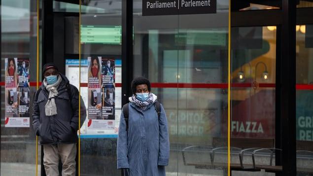 Deux personnes portant le masque attendent à l'arrêt d'autobus.