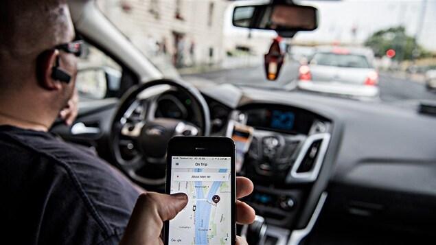 Dans une voiture un homme est volant pendant qu'une autre personne présente montre l'application Uber à partir d'un téléphone