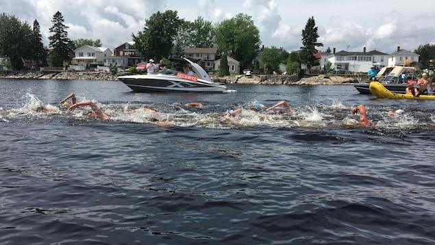 Des nageurs font la course dans l'eau vive.