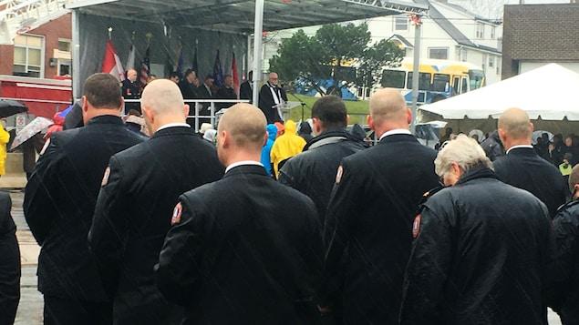 Des pompiers assistent sous la pluie à une cérémonie.