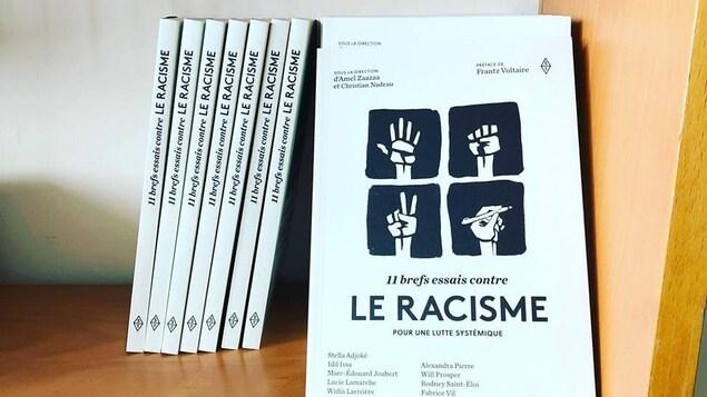 Une pile de livres dans une bibliothèque. L'un deux montre une illustration avec quatre mains; une faisant un signe de paix, l'autre entre-ouverte, l'autre fermée en poing et une autre tenant un crayon.