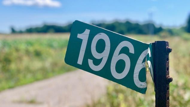 Un pancarte en métal sur laquelle est écrit 1966 devant un champs.