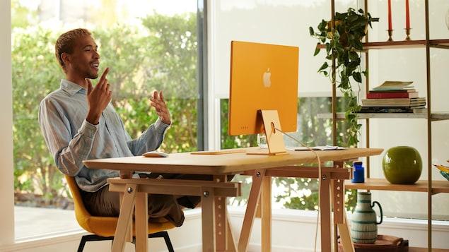 Un homme parle devant son écran d'ordinateur, posé sur un bureau.
