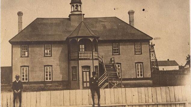 Deux hommes appuyés sur une clôture en avant plan avec en arrière-plan un bâtiment en bois à deux étages avec un clocher sur le toit au-dessus de la porte principale située au centre de la façade de l'édifice.