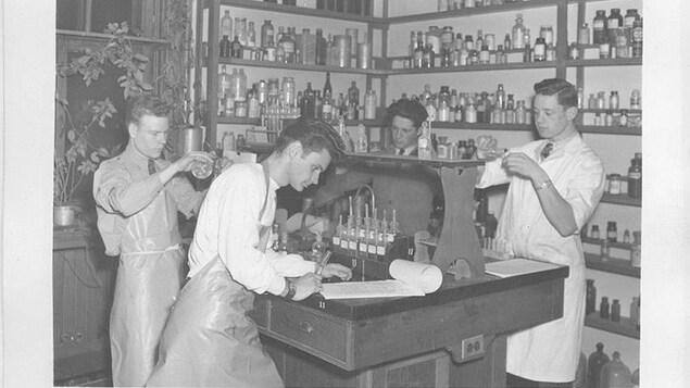 Quatre jeunes hommes sont au travail dans un laboratoire. Ils sont autour d'une table où se trouvent des instruments, deux mesurent des substances, un autre prend des notes. Autour d'eux se trouvent des étagères remplies de fioles et de bouteilles diverses.