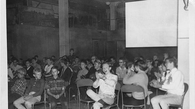 Plusieurs élèves sont assis sur des chaises en métal dans une salle et applaudissent. Il y a derrière eux un écran blanc.