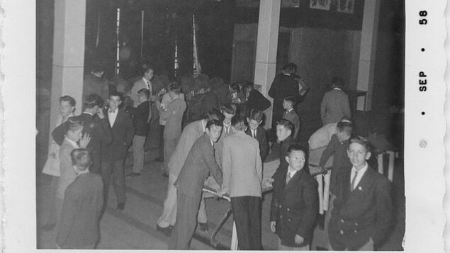Plusieurs petits groupes de jeunes garçons, qui s'amusent ou discutent dans une salle. À l'avant-plan à droite, un élève portant des lunettes en regarde un autre. qui lui regarde la caméra