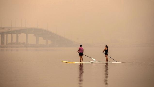 Deux pagayeuses circulent sur le lac Okanagan avec un épais brouillard autour d'elles.