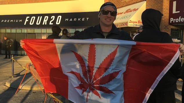 Un homme avec des lunettes de soleil arbore un drapeau canadien où une feuille de cannabis remplace la feuille d'érable.