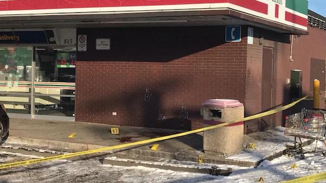Un dépanneur entouré de ruban jaune, avec des cercles de craie blanche marquant les points d'impact des balles de la police. Une flaque de sang est encore visible.