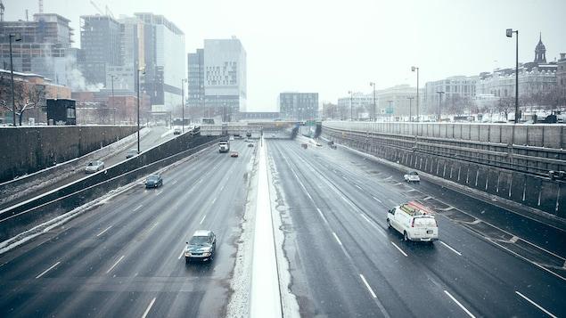 Quelques véhicules circulent sur l'autoroute Ville-Marie, au centre-ville de Montréal, près du nouveau CHUM, en hiver.