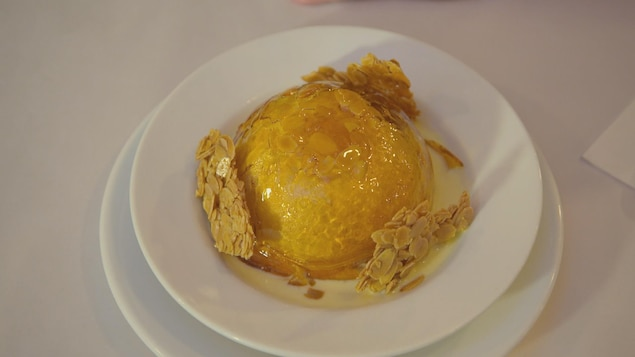 Une portion du dessert île flottante dans un bol blanc.