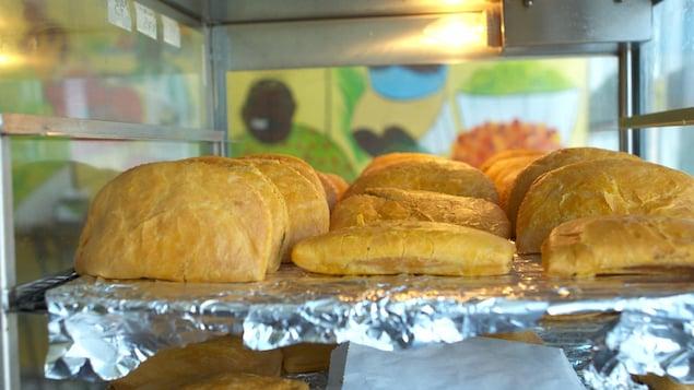 Trois rangées de pâtés jamaïcains dans un réchaud, sur une feuille d'aluminium.