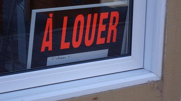 """Une affiche """"à louer"""" dans une fenêtre."""