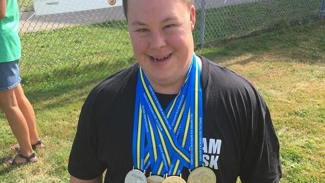 Un jeune homme regarde l'objectif en souriant, quatre médailles pendent à son cou.