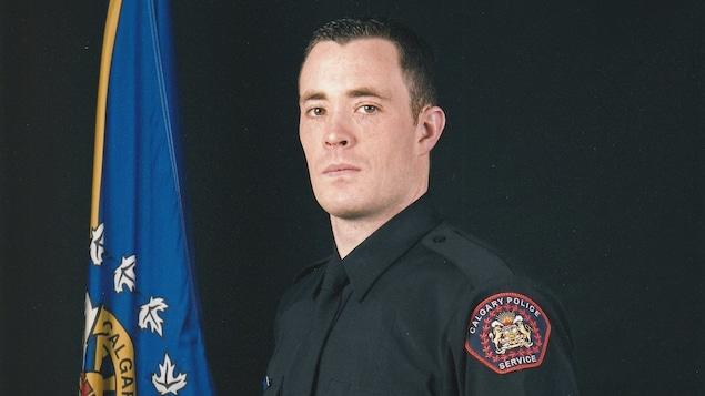 Photo officielle du sergent Andrew Harnett en uniforme de police, devant un drapeau de Calgary.