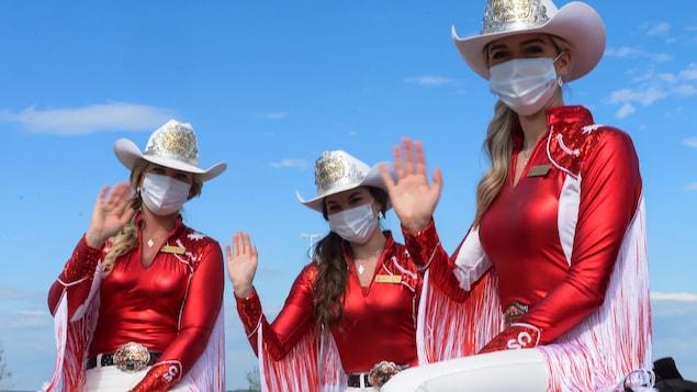Trois princesses du Stampede saluent la caméra, portant leur habit d'apparat et un masque chirurgical lors du déjeuner aux crêpes au volant, le 4 juillet 2020.