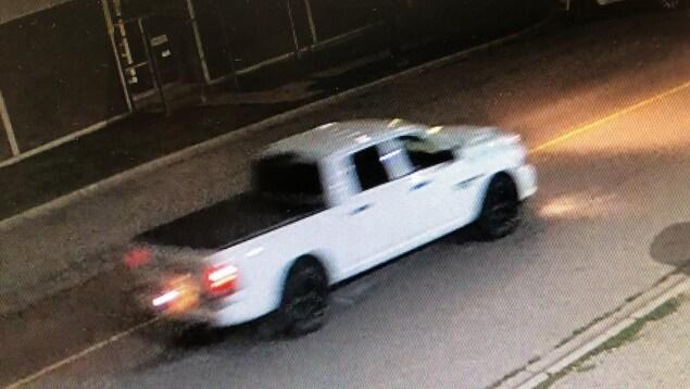 Une camionnette blanche circule dans la rue, le soir.
