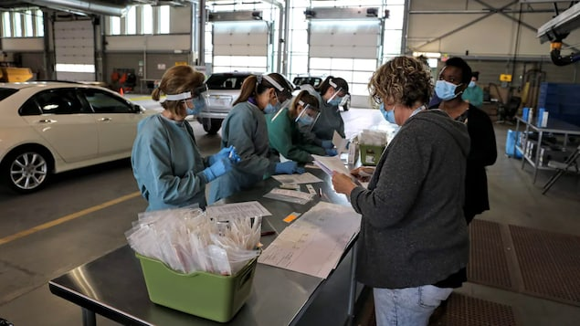 Du personnel médical regarde des papiers autour d'une table sur laquelle sont posés des ensembles de tests, dans un garage.