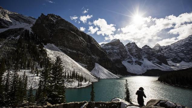 Une femme est au bord d'un lac bordé de montagnes et de conifères enneigés, par une journée ensoleillée.